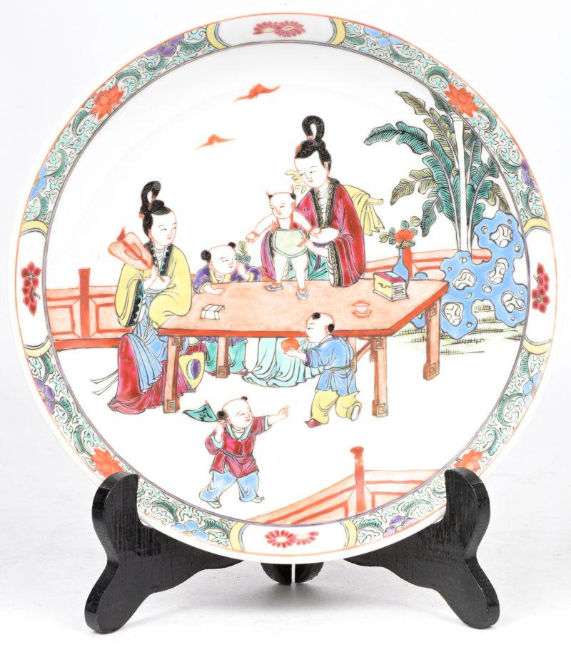 Een bordje van Chinees porselein met een famille rose decor van een familiescène. Onderaan Qinglong merk in blauw onder glazuur.