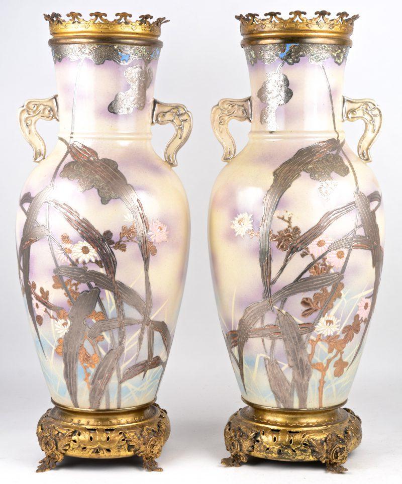 Een paar aardewerken vazen met meerkleurig en verguld decor van planten en met messingen monturen.
