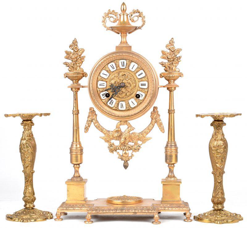 Een koperen schouwpendule in empirestijl. Bijgevoegd twee bronzen kandelaars in barokke stijl.