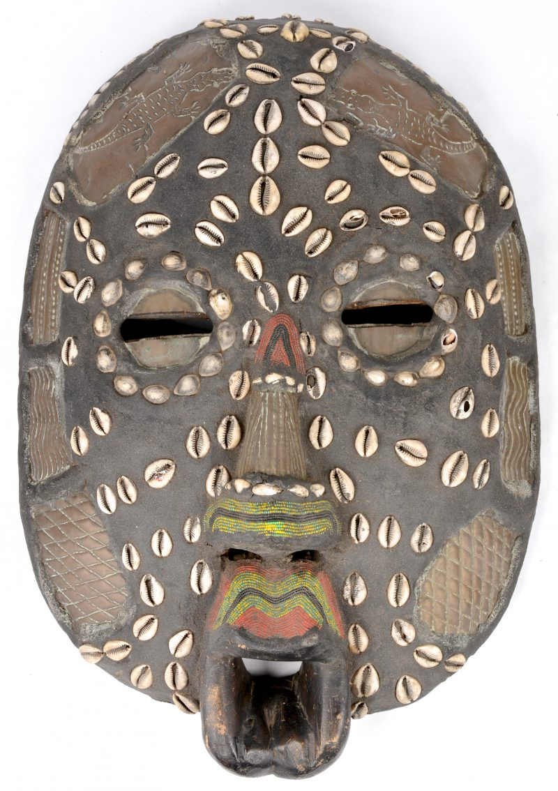 Een Afrikaans houten masker, versierd met schelpjes, koper en kraaltjes.