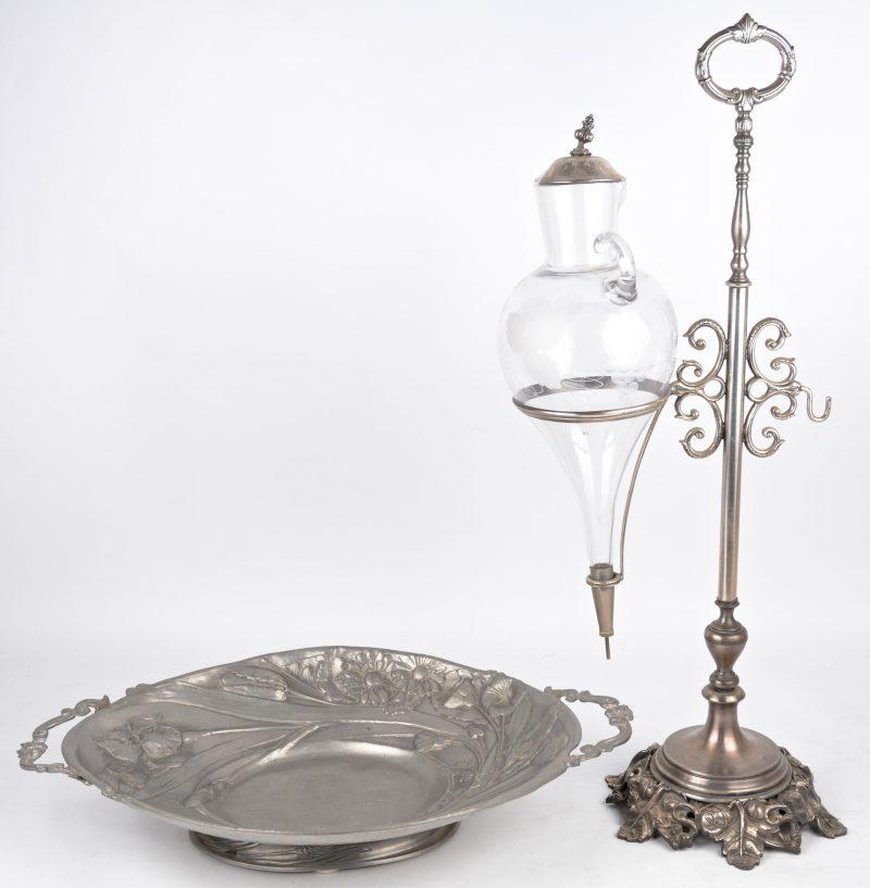 Een glazen wijnkaraf in tinnen houder en een art nouveau tinnen schotel.