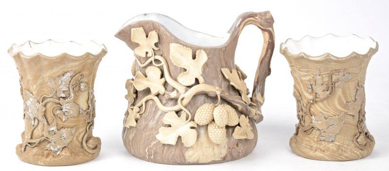 Twee vaasjes en een kannetje van aardewerk met een reliëfdecor van bessen. Onderaan gemerkt.