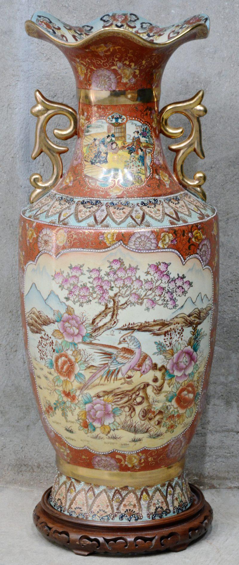 Een grote vaas van Satsuma-aardewerk met een meerkleurig en verguld decor van fazanten en pioenen. Op houten sokkel.