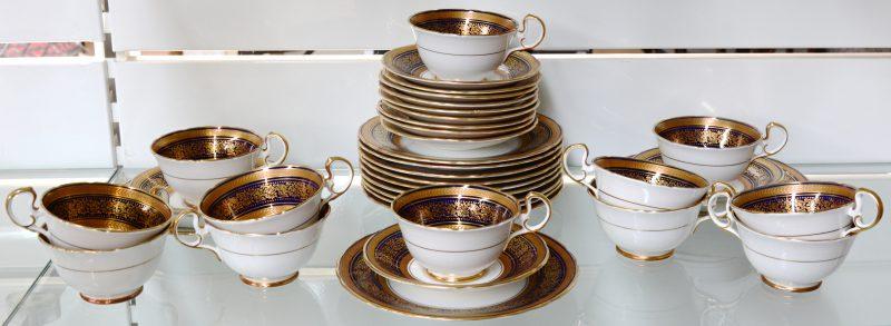 Een Engels theeservies  van wit, kobaltblauw en verguld porselein, bestaande uit theekopjes met onderschoteltjes en met bordjes. Compleet voor twaalf personen.