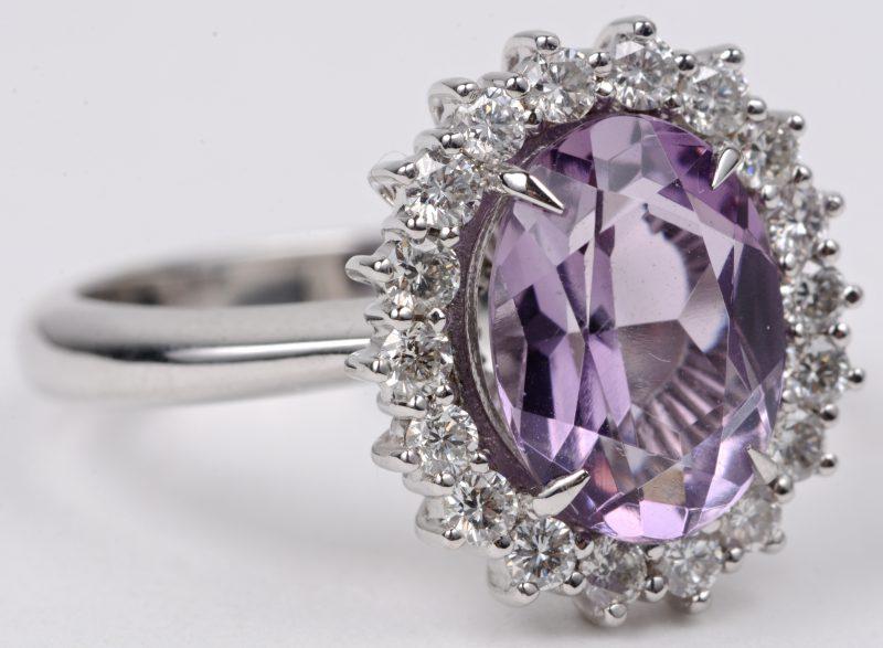 Een 18 karaats wit gouden ring bezet met diamanten met een gezamenlijk gewicht van ± 0,65 ct. en een centrale amethist van ± 2,60 ct.
