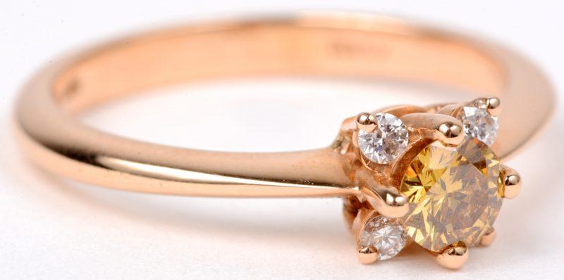 Een 18 karaats roze gouden ring bezet met diamanten met een gezamenlijk gewicht van ± 0,10 ct. en een centrale gele diamant van± 0,25 ct.
