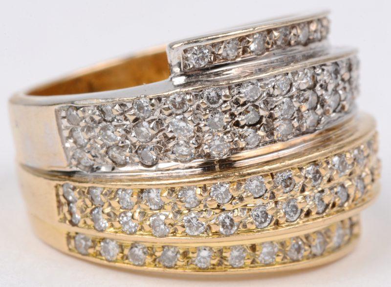 Een 18 karaats wit en geel gouden ring bezet met briljanten met een gezamenlijk gewicht van ± 1,20 ct.