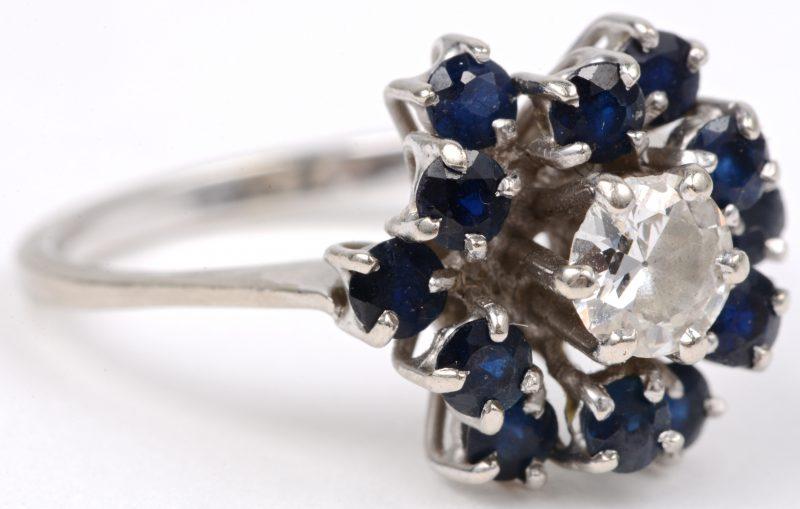 Een 18 karaats wit gouden ring bezet met saffieren met een gezamenlijk gewicht van ± 0,50 ct. en een centrale diamant van ± 0,50 ct.