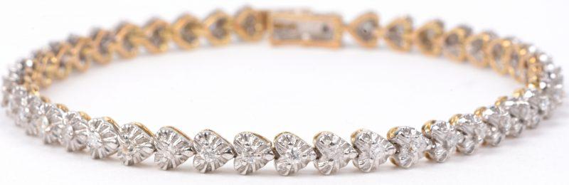 Een 14 karaats wit en geel gouden armband bezet met briljanten met een gezamenlijk gewicht van ± 1 ct.