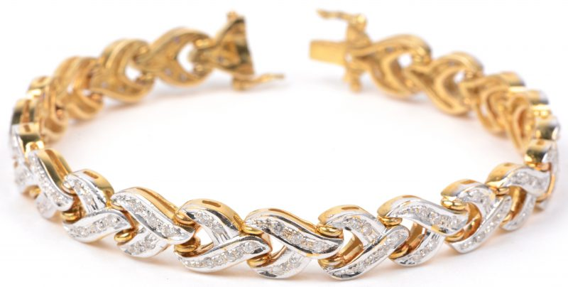 Een 14 karaats wit en geel gouden armband bezet met briljanten met een gezamenlijk gewicht van ± 1,10 ct.