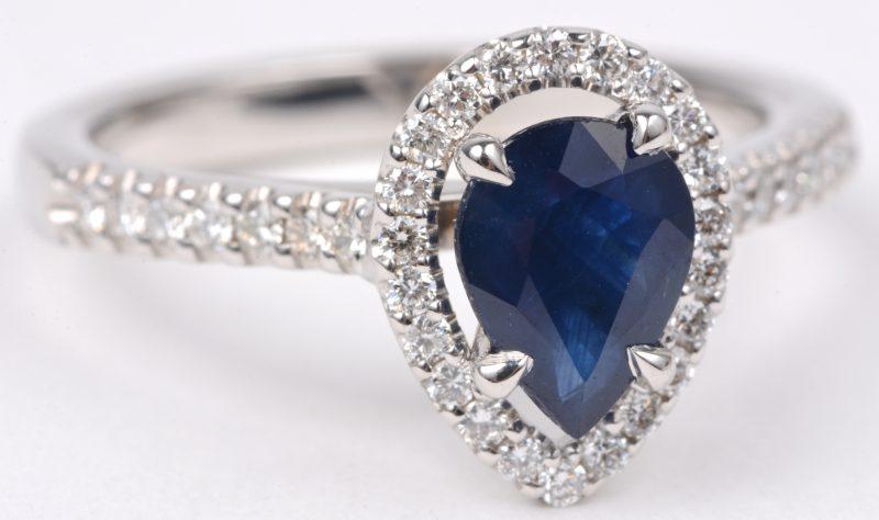 Een 18 karaats wit gouden ring bezet met diamanten met een gezamenlijk gewicht van ± 0,35 ct. en een centrale saffier van ± 1 ct.