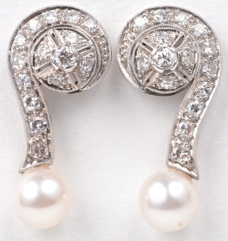 Een paar 18 karaats wit gouden oorbellen bezet met diamanten met een gezamenlijk gewicht van ± 0,80 ct. en twee parels.