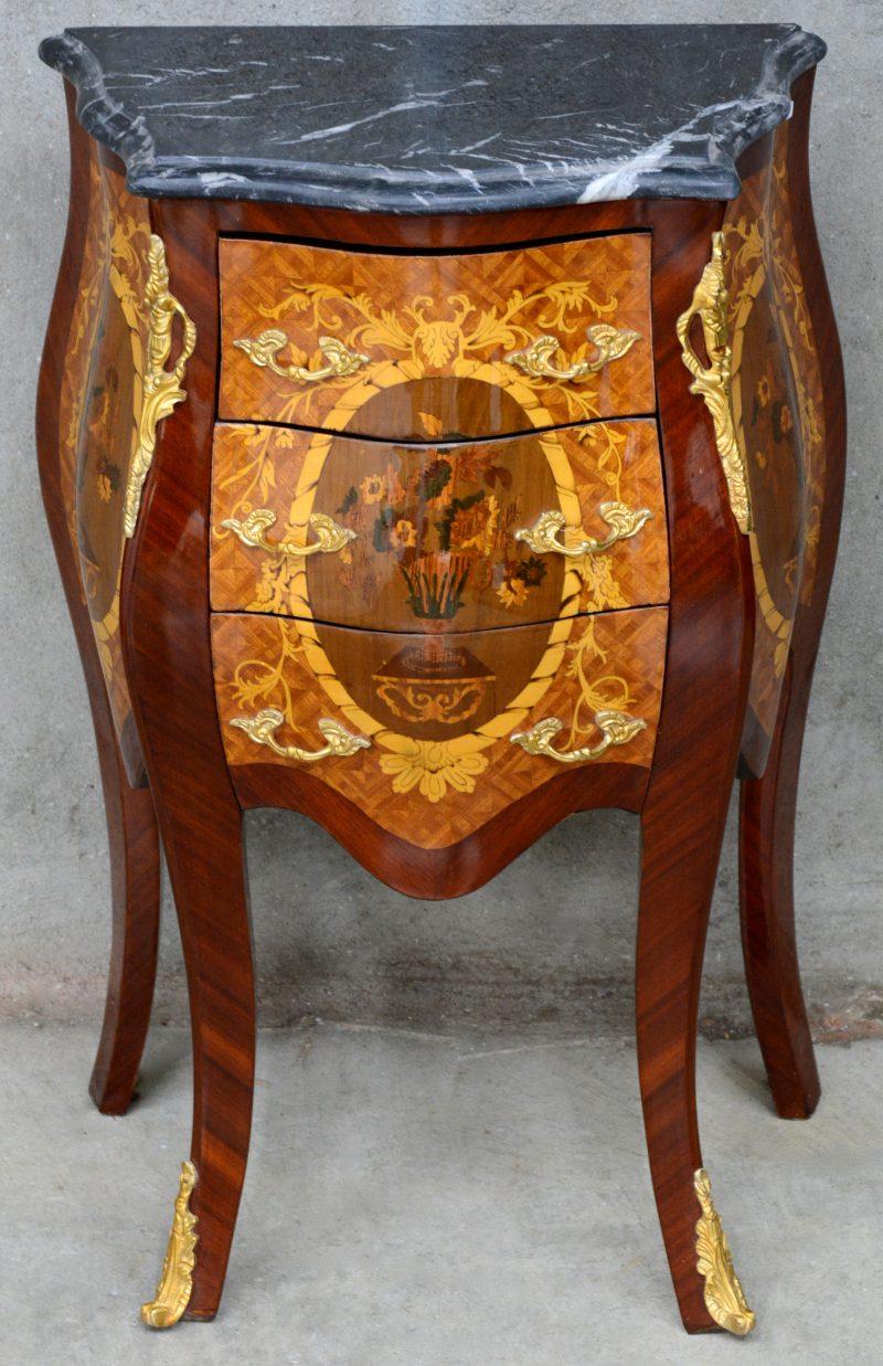 Een kleine commode in Lodewijk XV-stijl met drie laden, versierd met marquetterie en met een zwart marmeren blad.