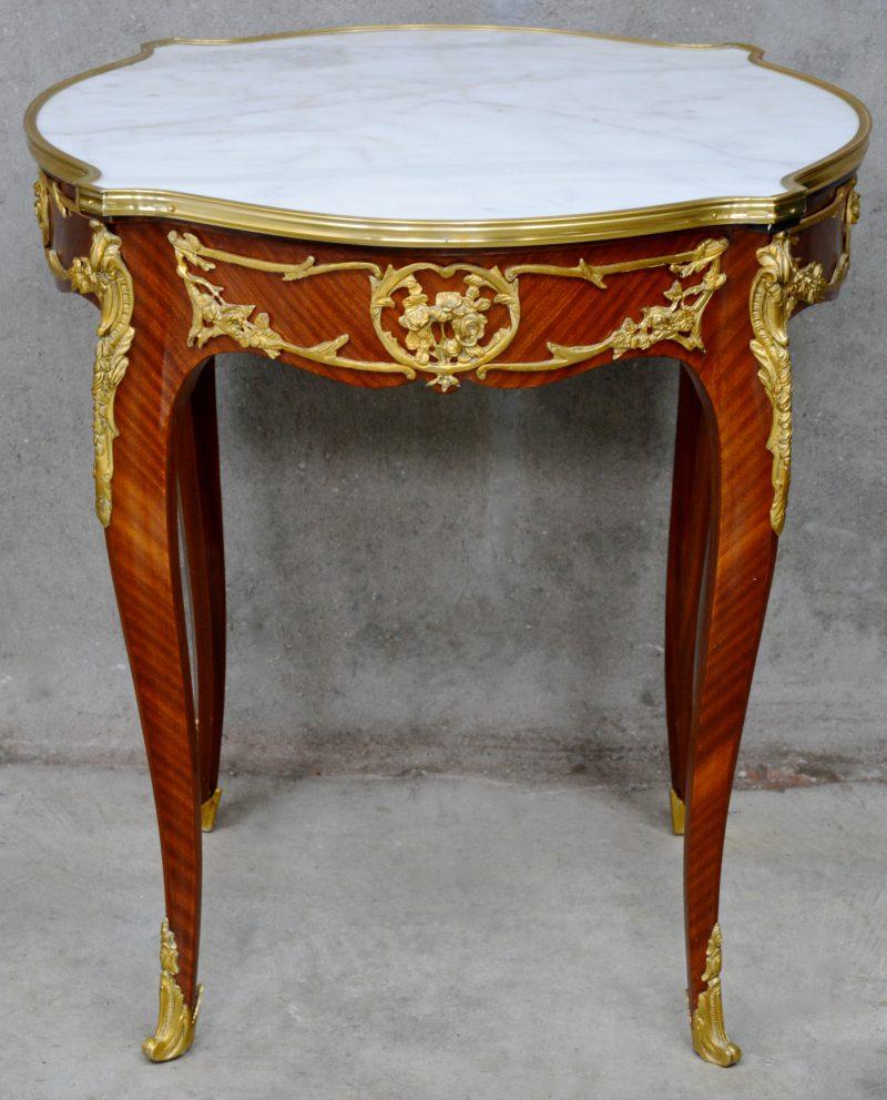 Een gefineerde tafel, versierd met verguld bronsbeslag en met een wit marmeren blad.