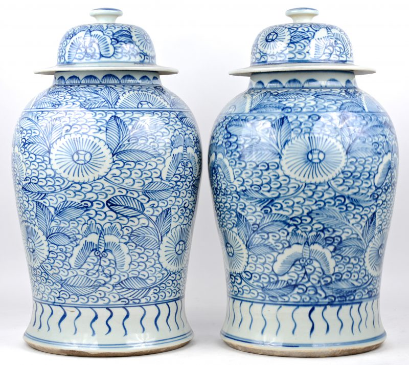 Een paar dekselvazen van Chinees porselein met een blauw op wit bloemendecor.