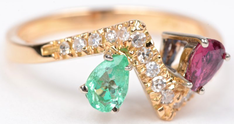 Een 18 karaats geel gouden ring bezet met diamanten met een gezamenlijk gewicht van ± 0,20 ct. een robijn van ± 0,20 ct. en een smaragd van ± 0,25 ct.