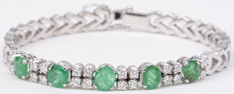 Een 18 karaats wit gouden schakelarmband bezet met diamanten met een gezamenlijk gewicht van ± 1 en smaragden met een gezamenlijk gewicht van ± 1 ct.