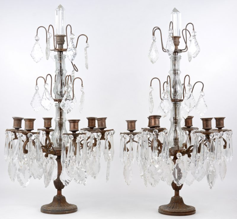 Een paar bronzen girandoles met zes lichtarmen en met kristallen pendeloques.