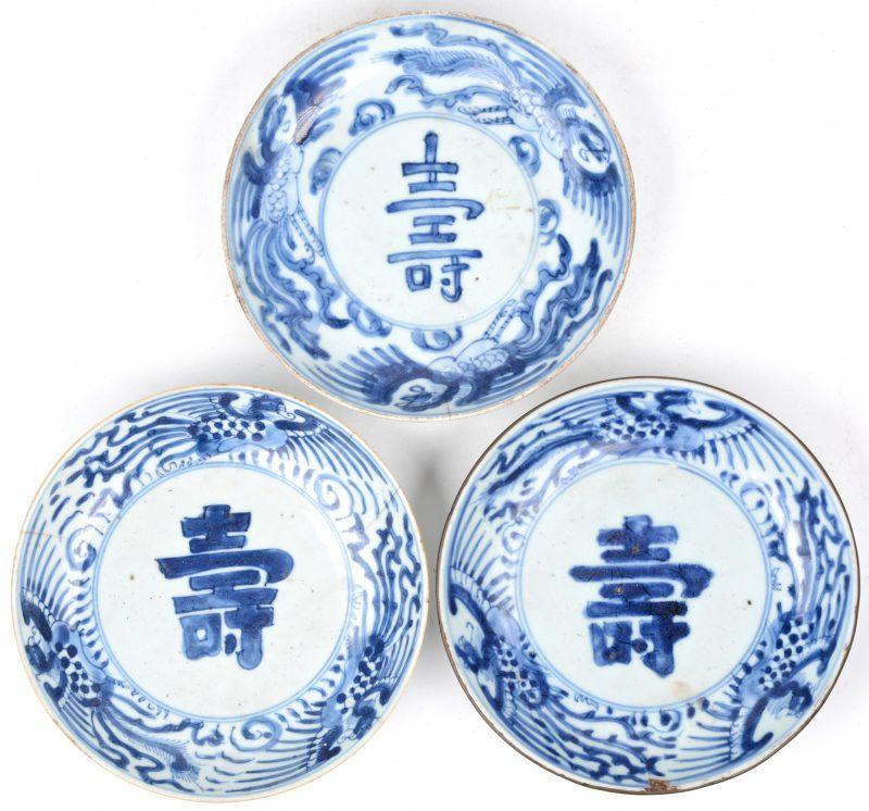 Drie schoteltjes van Chinees porselein met een blauw op wit decor. Haarscheuren en schilfers.