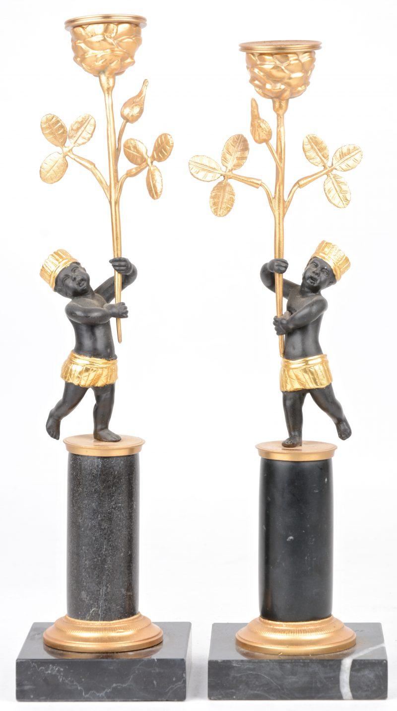 Een paar deels verguld bronzen kandelaartjes, gedragen door moriaantjes op arduinen sokkeltjes.