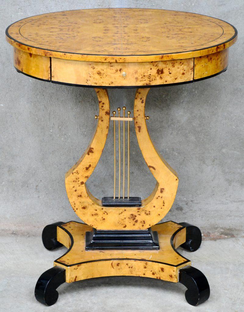 Een ovale tafel van wortelfineer met één laten en op liervormige voet.