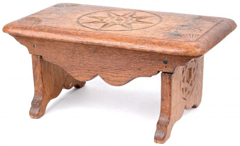 Een antiek gebeeldhouwd houten voetenbankje.