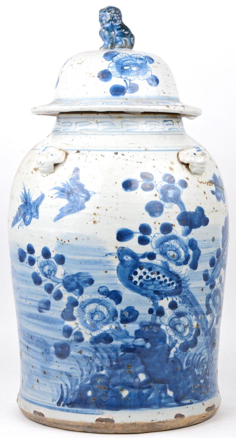 Een dekselvaas van Chinees porselein met een blauw op wit decor van bloesems en vogels en het deksel getooid met een Fo-hond.