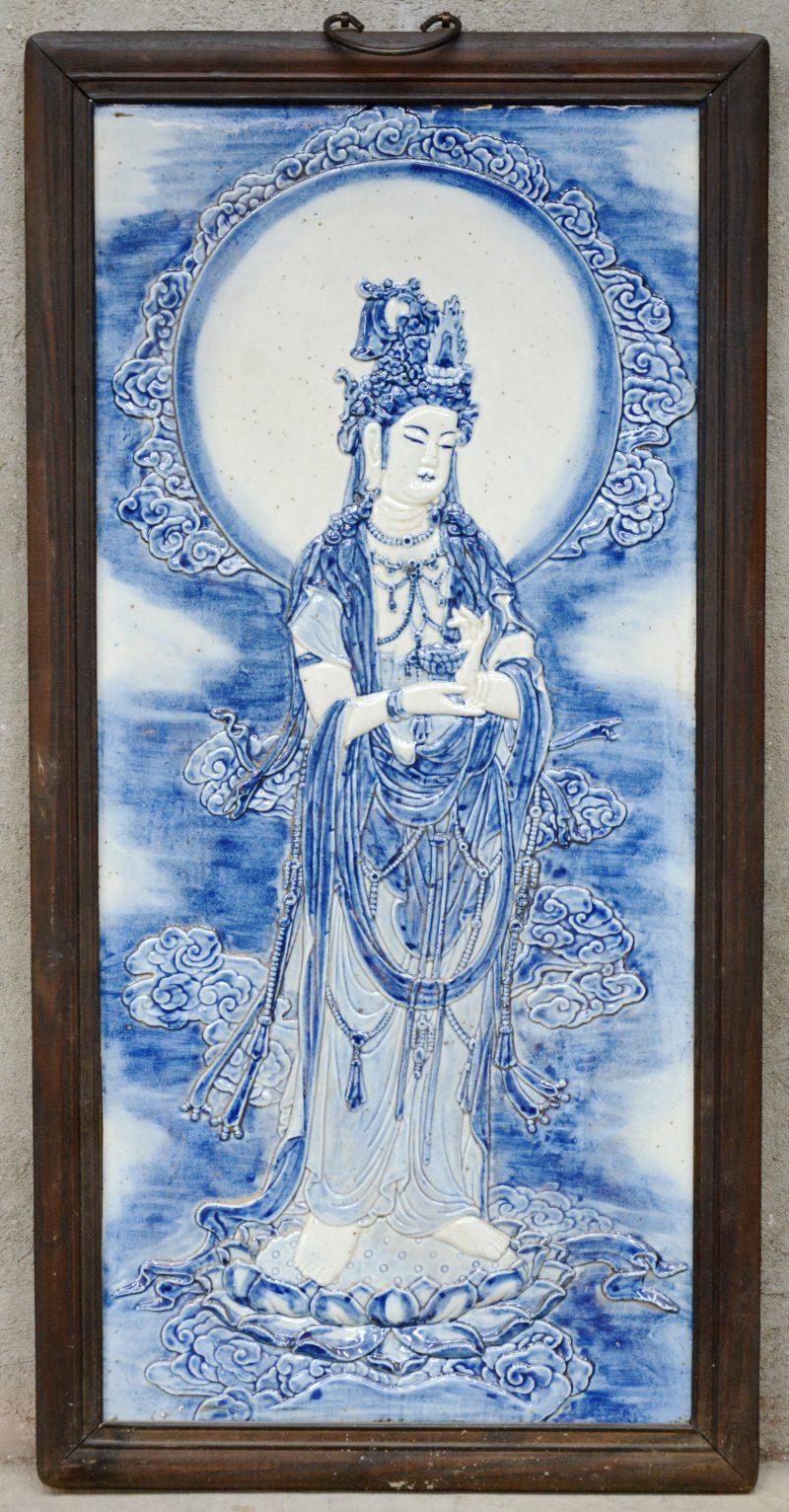 Een Chinese wandplaquette van blauw en wit porselein met een voorstelling van een Guanyin in reliëf. In houten lijst.