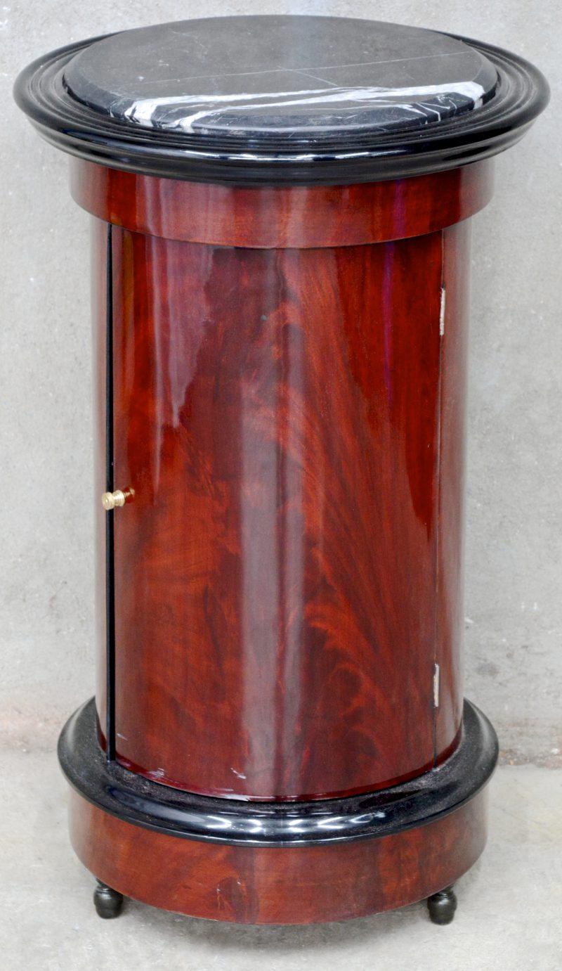 Een rond bijzetkastje van mahoniehoutfineer met één lade en een zwart marmeren blad.
