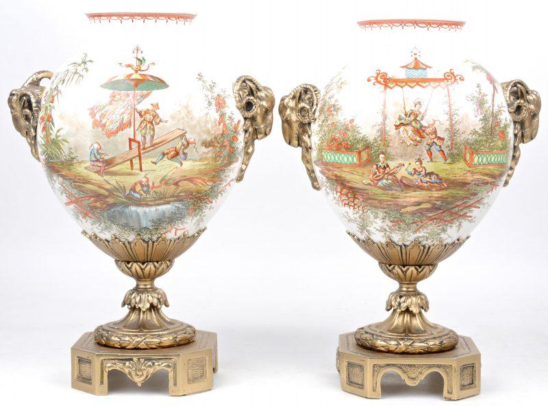 Een paar siervazen van aardewerk met meerkleurig Chinoiseriedecor. Op bronzen voet en met twee bronzen ramskoppen.