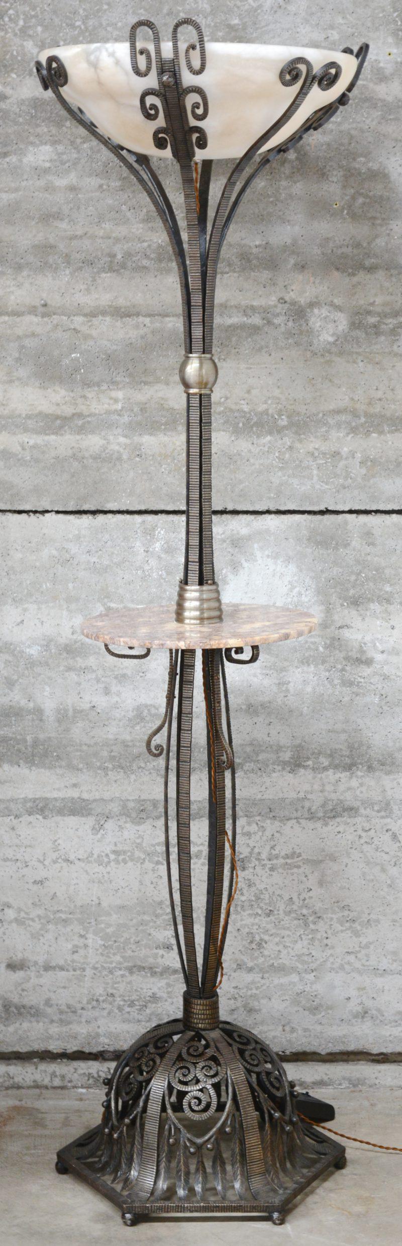 Een smeedijzeren art deco stijl staande lamp met grote glazen coupe en een marmeren blad. Naar Majorelle.