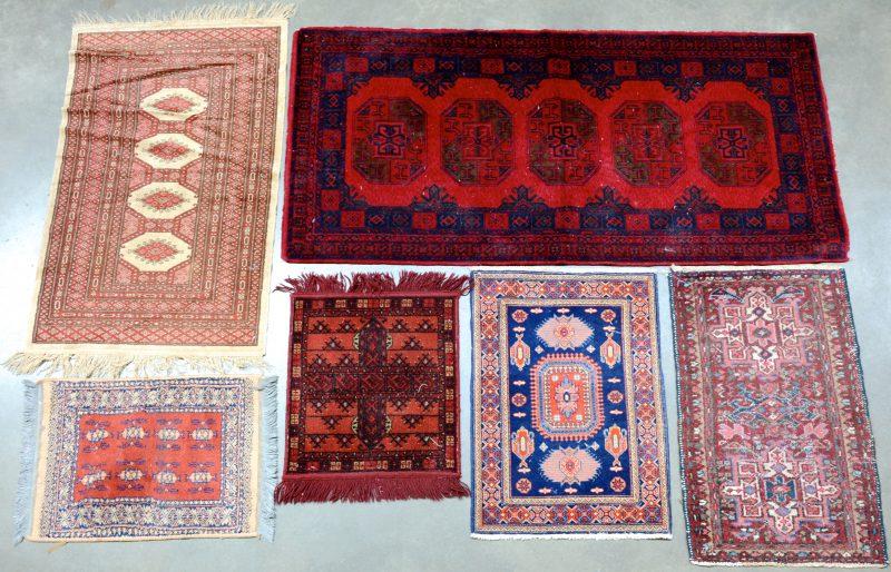 Een lot van zes wollen tapijtjes.