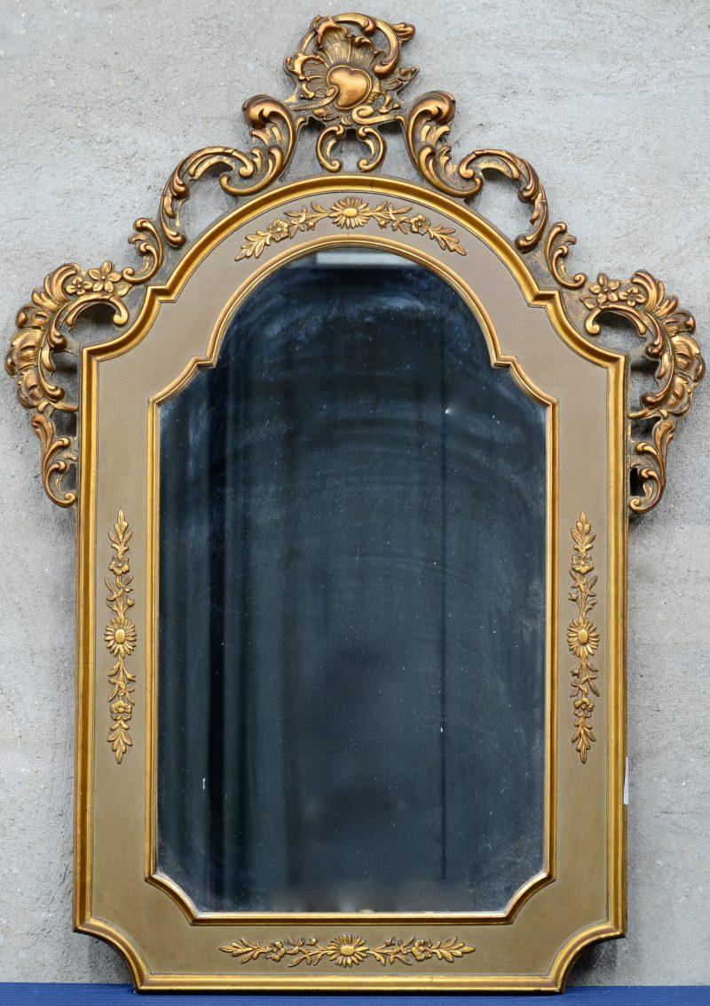 Een spiegel van verguld hout in barokke stijl met een rocaille in de kuif.