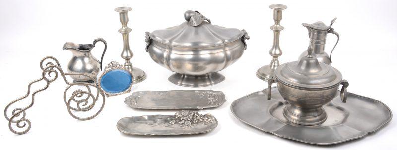Een lot tin, bestaande uit een terrine met schaal, een kannetje, een bonbonnière, twee art nouveau vide-poches en een paar kandelaars. We voege er een kannetje, een fotokadertje en een servethouder van verzilverd metaal aan toe.