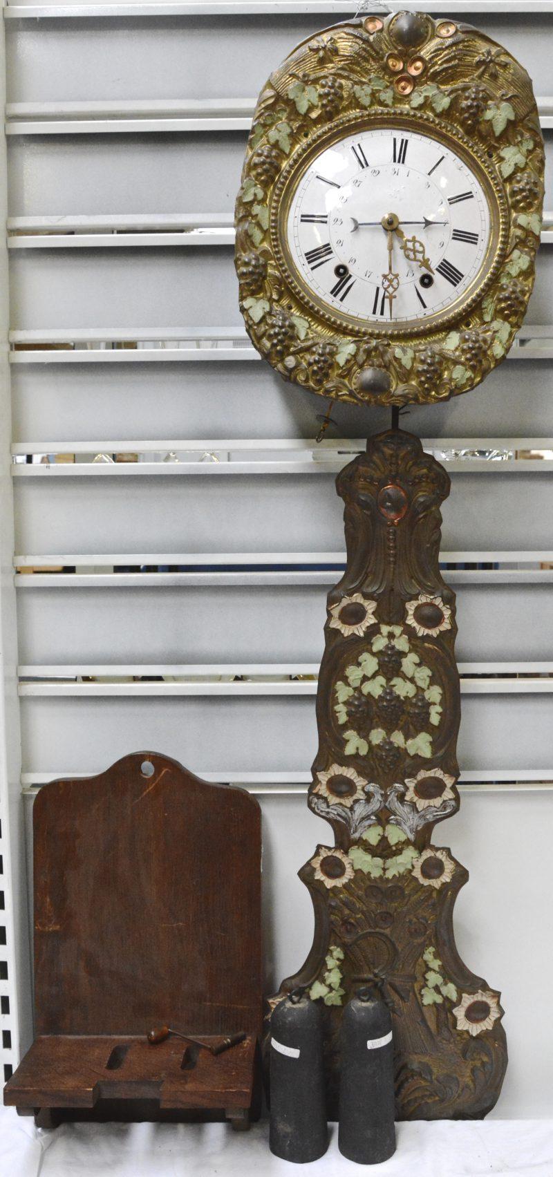 Een comtoiseklok van gedreven geel koper met een gepolychromeerd decor van druivenranken en korenhalmen. Compleet met sleutel en gewichten en op stoeltje.
