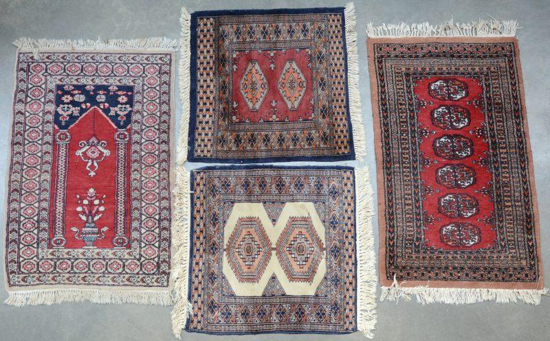 Een lot van vier handgeknoopte Oosterse bidkleedjes van wol en katoen.
