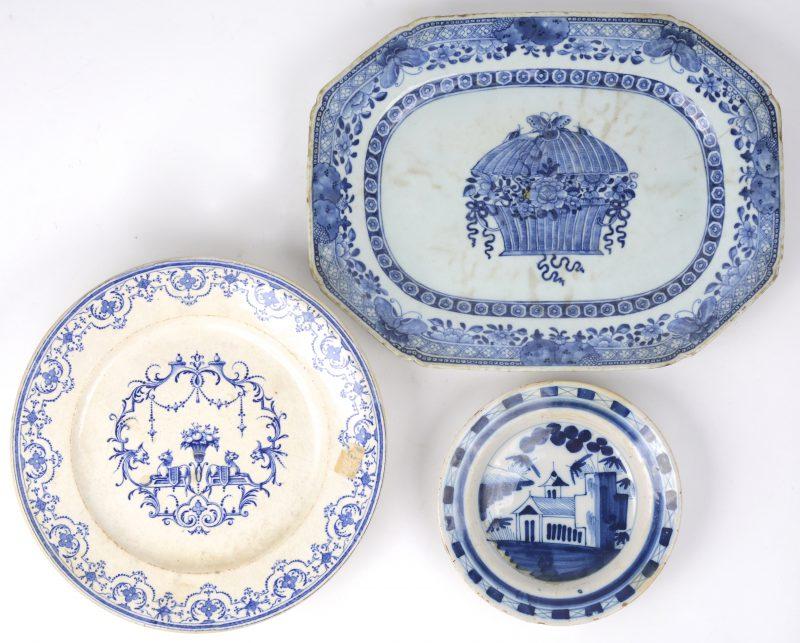 Drie aardewerken schotels: een klein Delfts bordje met een blauw en wit decor met een kerkje. XIXde eeuw. Een taartschotel van blauw en wit aardewerk. Onderaan gemerkt : Moustier. XIXde eeuw. Een achtkantige schotel van blauw en wit Chinees porselein (25 x 33 cm)(randslijtage en haarscheur). Tijdperk Tao Kuan.