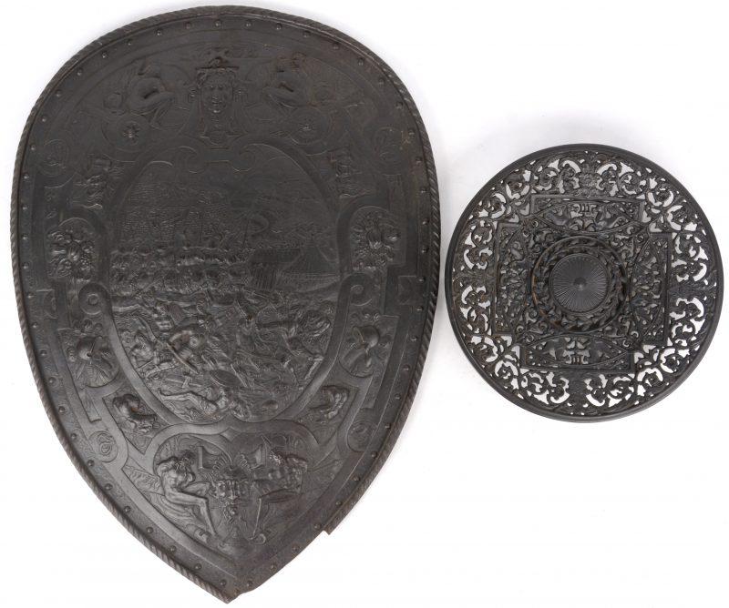 Een gietijzeren sierschild met een slagveldscène en heraldische symbolen in reliëf. Onderaan beschadigd. We voegen er een opengewerkte schaal, eveneens van gietijzer, aan toe.
