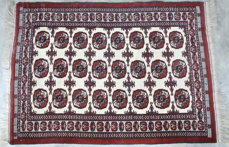 Een antiek handgeknoopt Oosters karpetje van wol met een Bocharamotief. Slijtage.