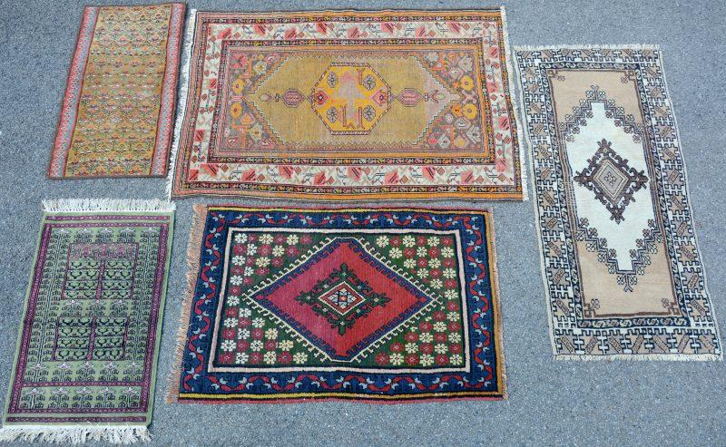 Een lot van vijf verschillende wollen karpetjes. Enkele met slijtage.