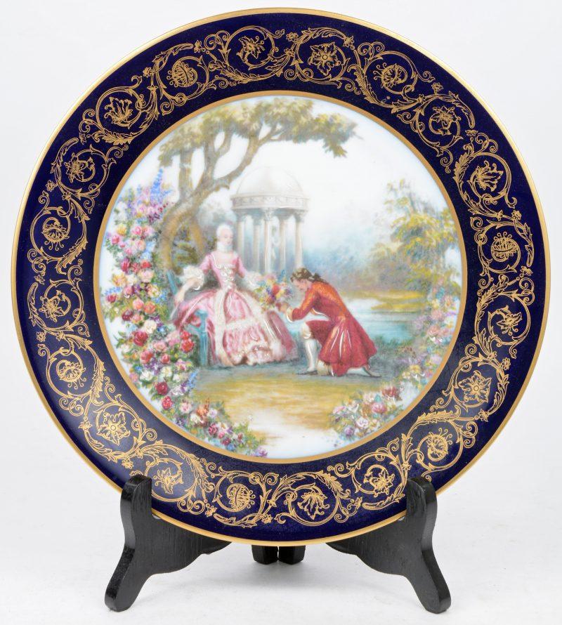 Een porseleinen sierbord met een met de hand opgehoogd meerkleurig decor van een romantisch koppel op een met verguldsel versierde kobaltblauwe fond.