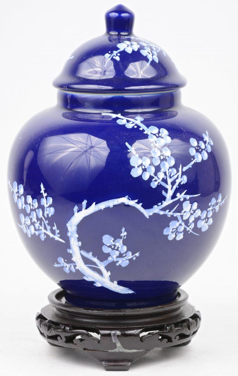 Een bol dekselvaasje met een wit decor van bloeiende takken op blauwe fond. Met houten sokkeltje. Onderaan gemerkt. Gerestaureerd.