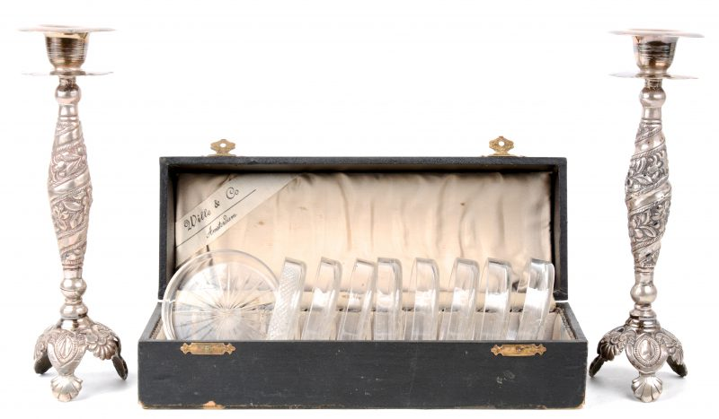 Een paar verzilverd koperen kandelaars met een gedreven bloemendecor.