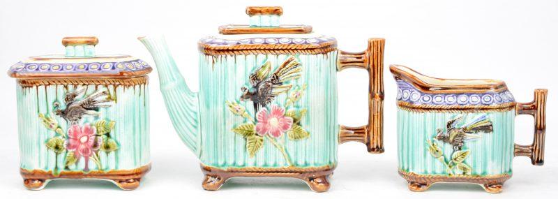 Een theeserviesje van meerkleurig aardewerk met een reliëfdecor van bloemen en vogels.