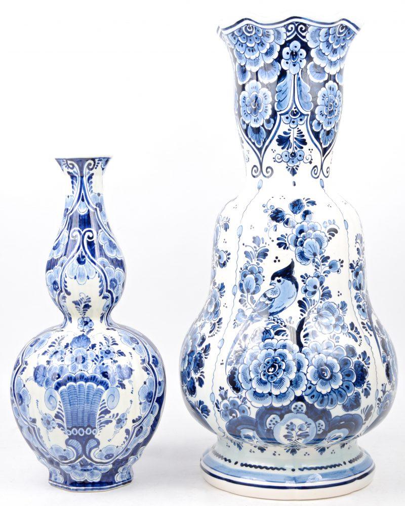 Twee verschillende vazen van Delfts aardewerk met blauw-witte bloemendecors. Onderaan gemerkt.