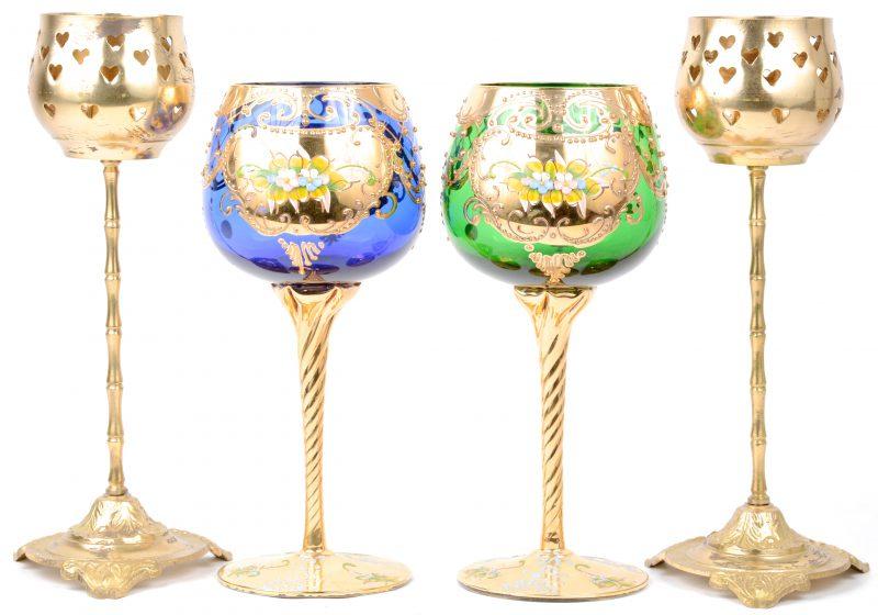 Twee wijnglazen, resp. met groene en blauwe kelk, versierd met vergulde motieven en meerkleurige bloemendecors. Bijgevoegd twee messingen kandelaars op voet.