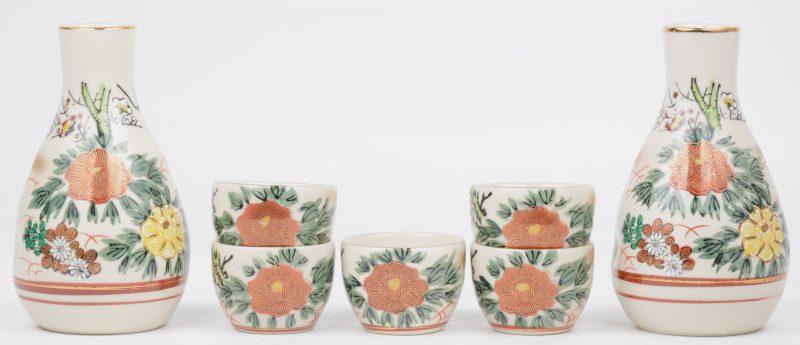 Twee porseleinen sakeflesjes met vijf kommetjes, versierd met bloemendecors en vergulde randen.