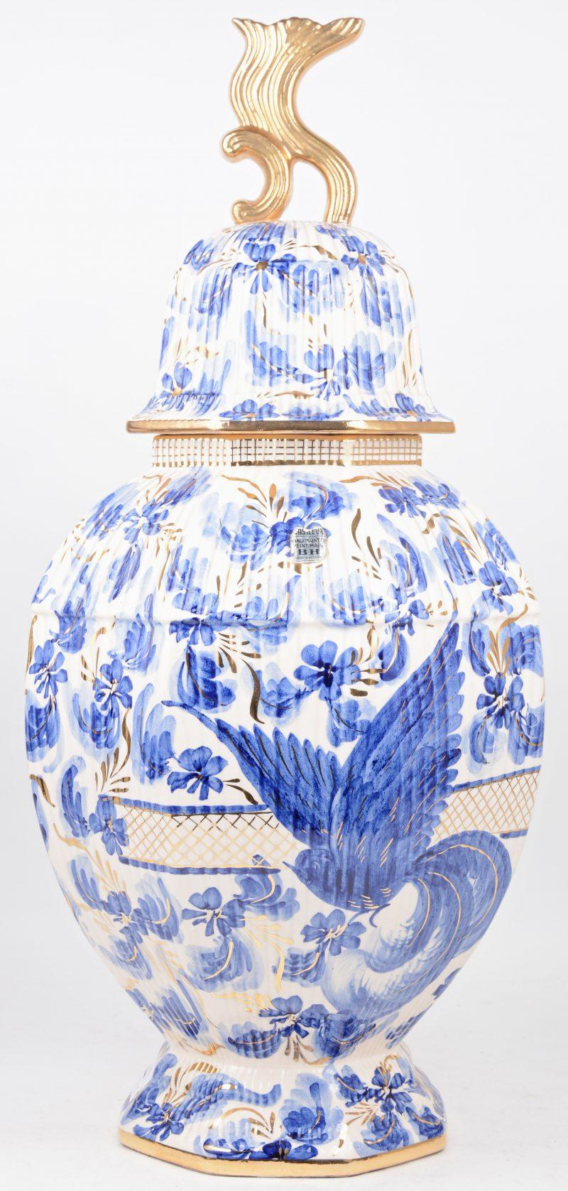 Een achthoekige dekselvaas van aardewerk met een blauw-wit en verguld bloemendecor. Schilfer aan het deksel.