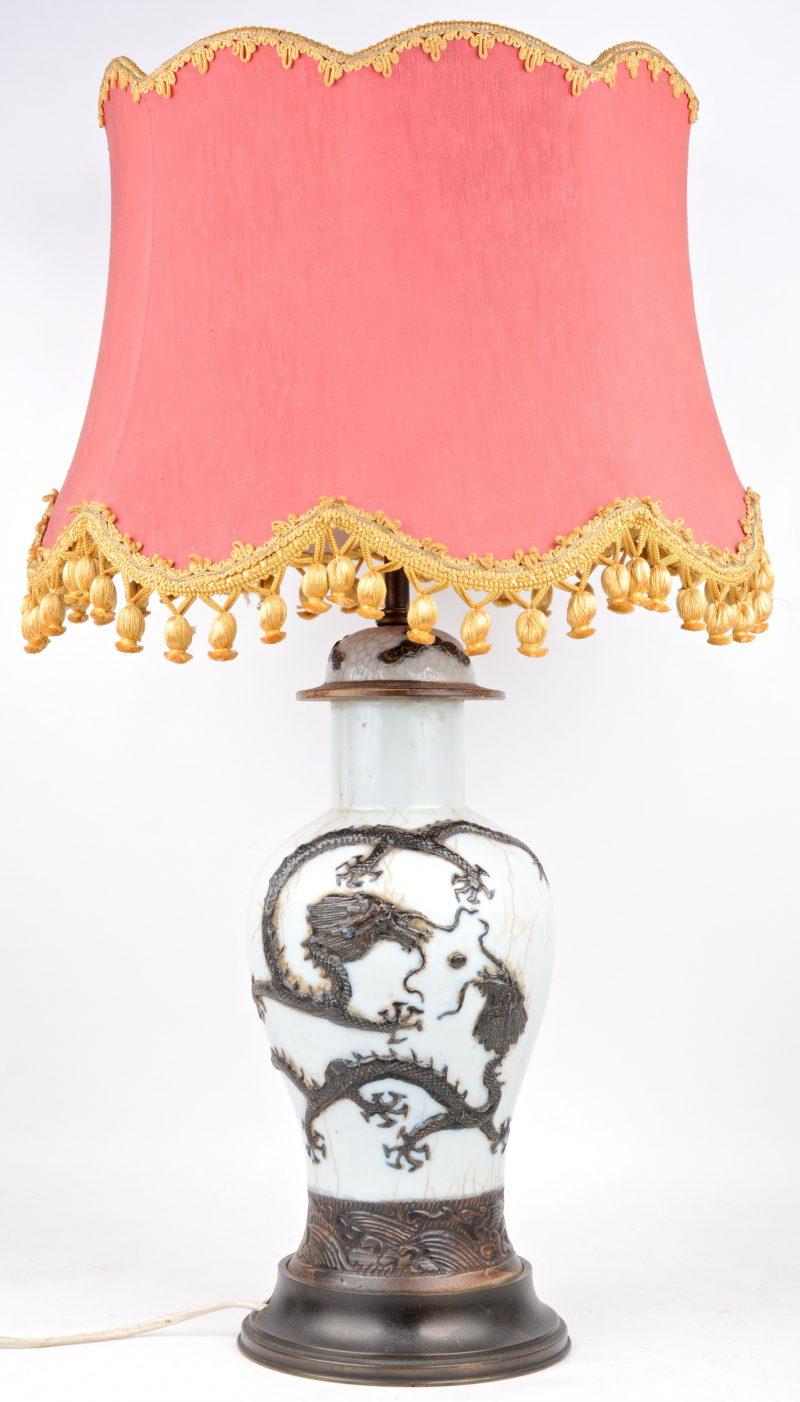 Een lampvoet van Chinees aardewerk in de vorm van een dekselvaas, gedecoreerd met een draak in reliëf.