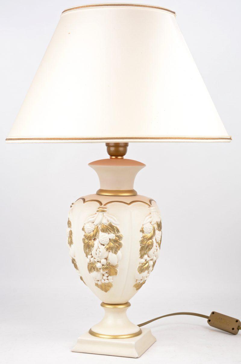 Een lampvoet van wit- en goudgepatineerd plaaster of terracotta. Achteraan gemerkt.